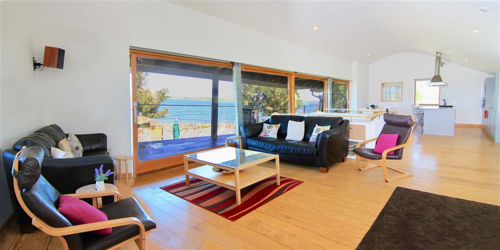 The lounge area with fantastic views of the sea. The sliding door to the balcony are next to the sofas