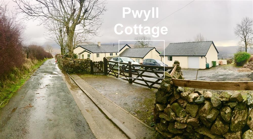 Photo from the road of double wooden gates to the Car Park area and of Pwyll Cottage