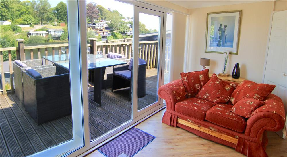 Lounge with large doors to the balcony. Behind this sofa is where the dining table and chairs are stored.