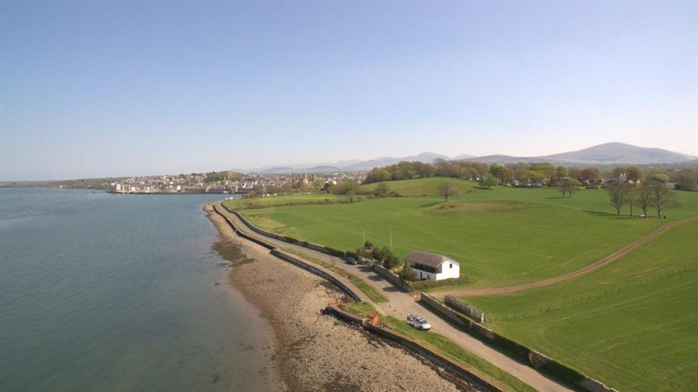 Bath Cottage is on the Menai Straits looking towards the island of Anglesey. In this photo you can see the town of Caernarfon in the distance.