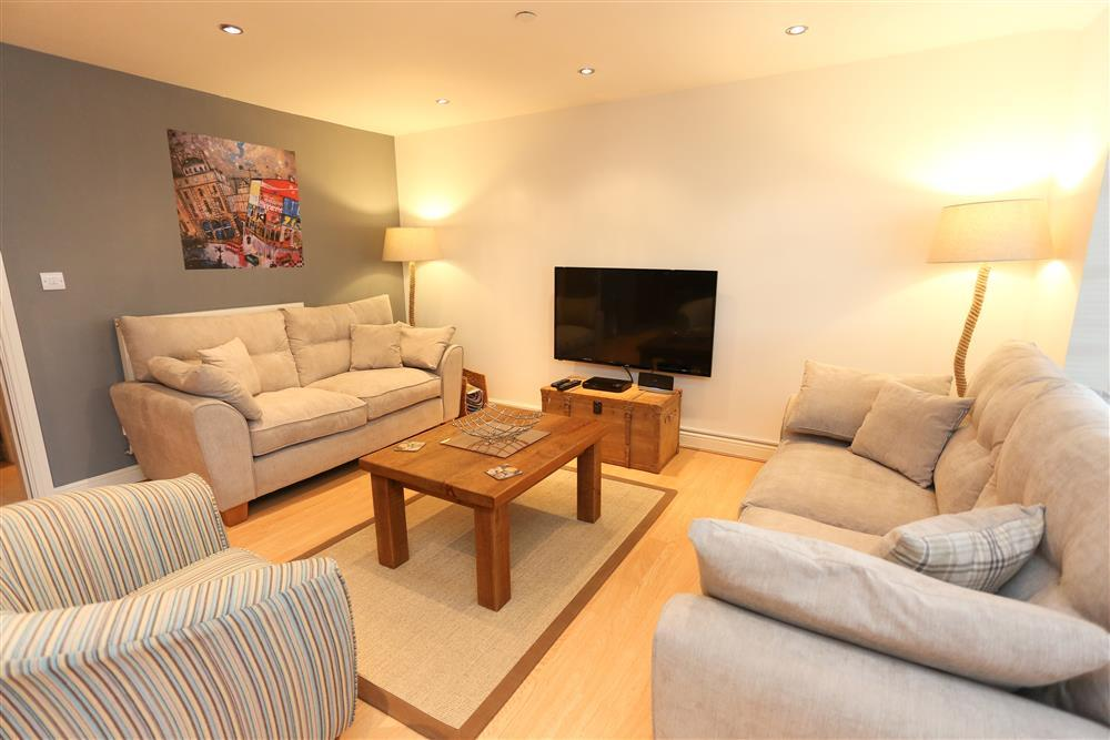 Spacious lounge with large TV and comfy seating