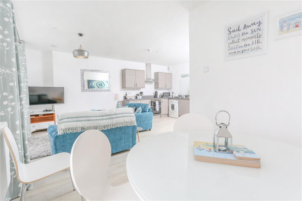 The living room has a dining area, lounge and kitchen with views out to sea