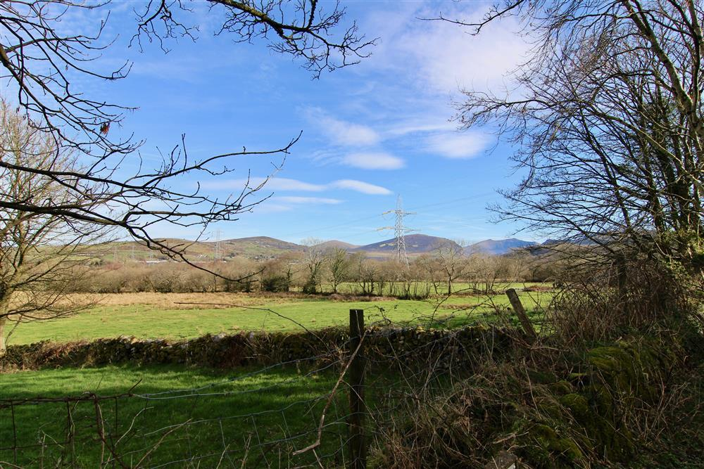 View from the front of the cottage of countryside with the hills 'Clogwyn Melyn' and 'Mynydd y Cilgwyn' in the distance.