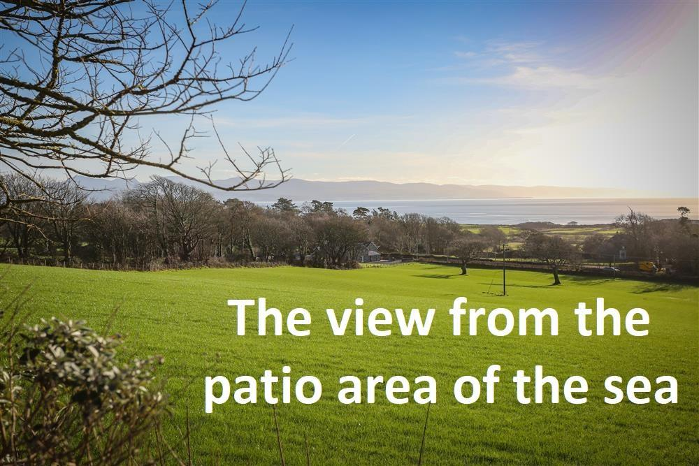 The view from the patio area outside the front door ofMin y Mor. Beyond the fields you can see the sea and far in the distance you can see Harlech area and the mountains of southern Snowdonia.