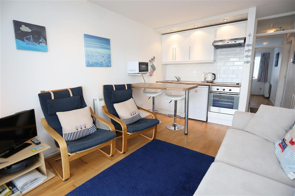 Lounge with comfy seating and kitchen area, including breakfast bar with seating