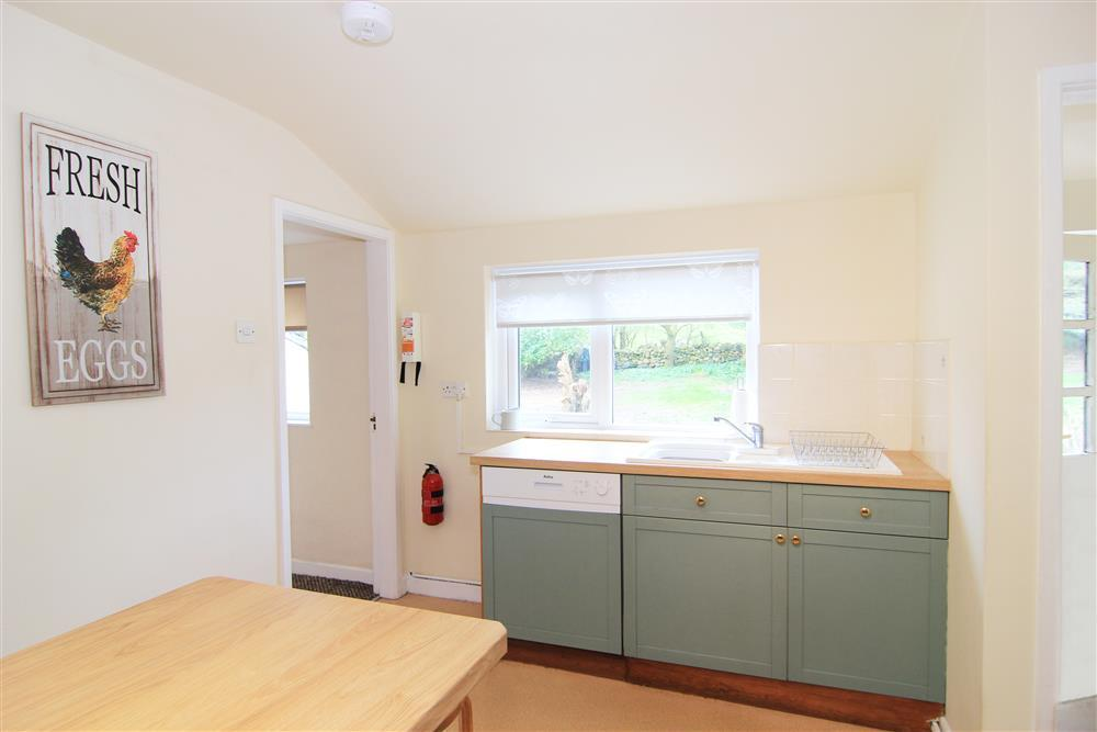 Kitchen area with breakfast bar with a door to the back garden
