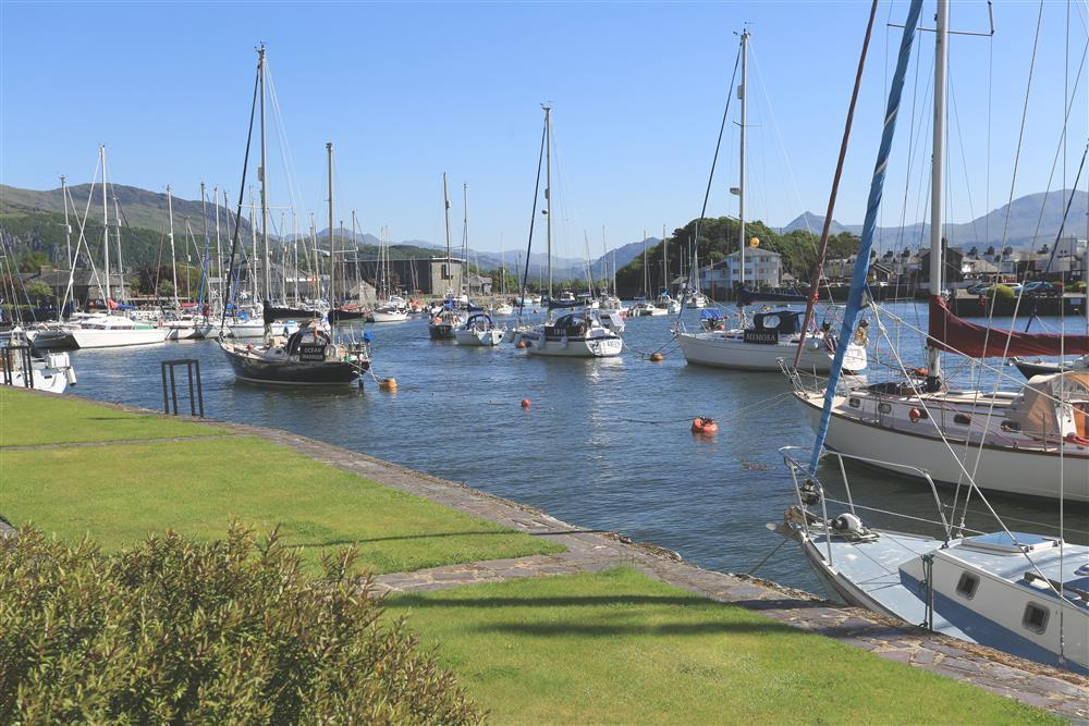 The view of Porthmadog Harbour and the boats with Snowdonia mountains in the distance