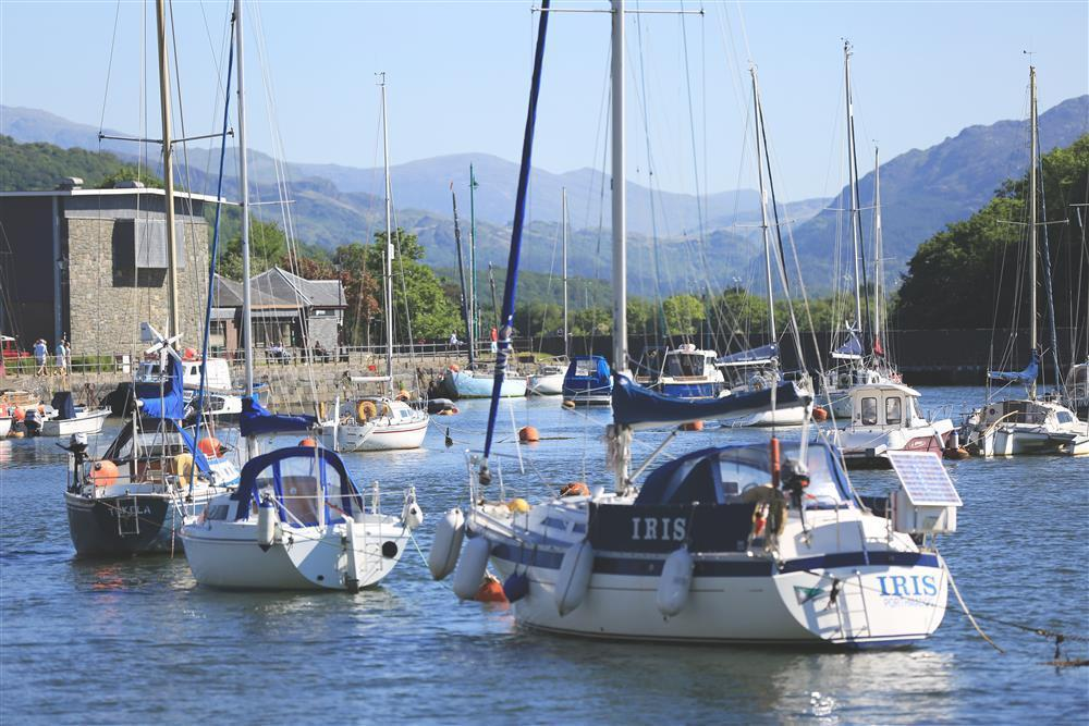 Close up photo of the boats in Porthmadog Harbour with Snowdonia mountains in the distance