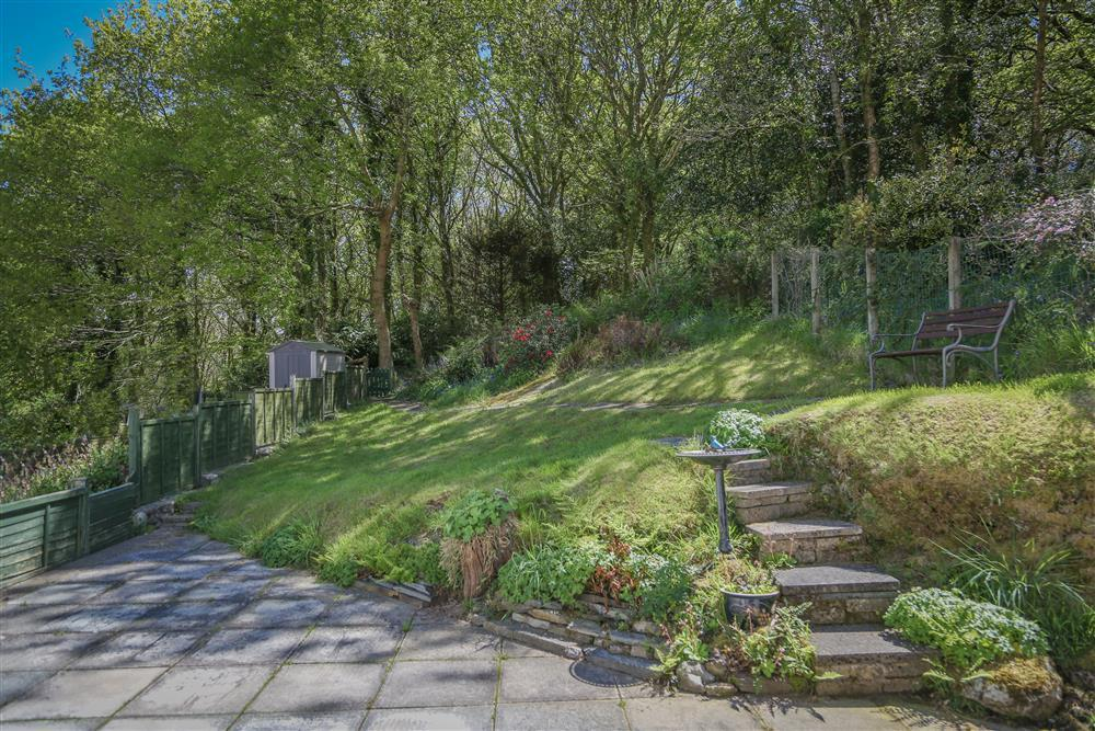 Garden and patio with a footpath going into the woods.