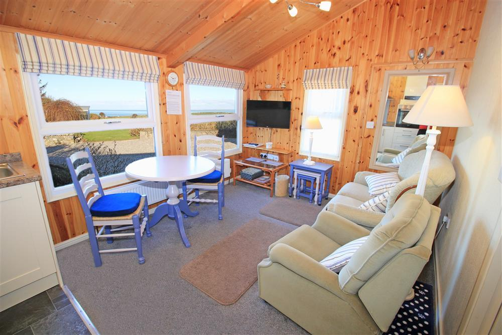 Living Room - Lounge area with dining table and chairs. Views of the sea from this room.