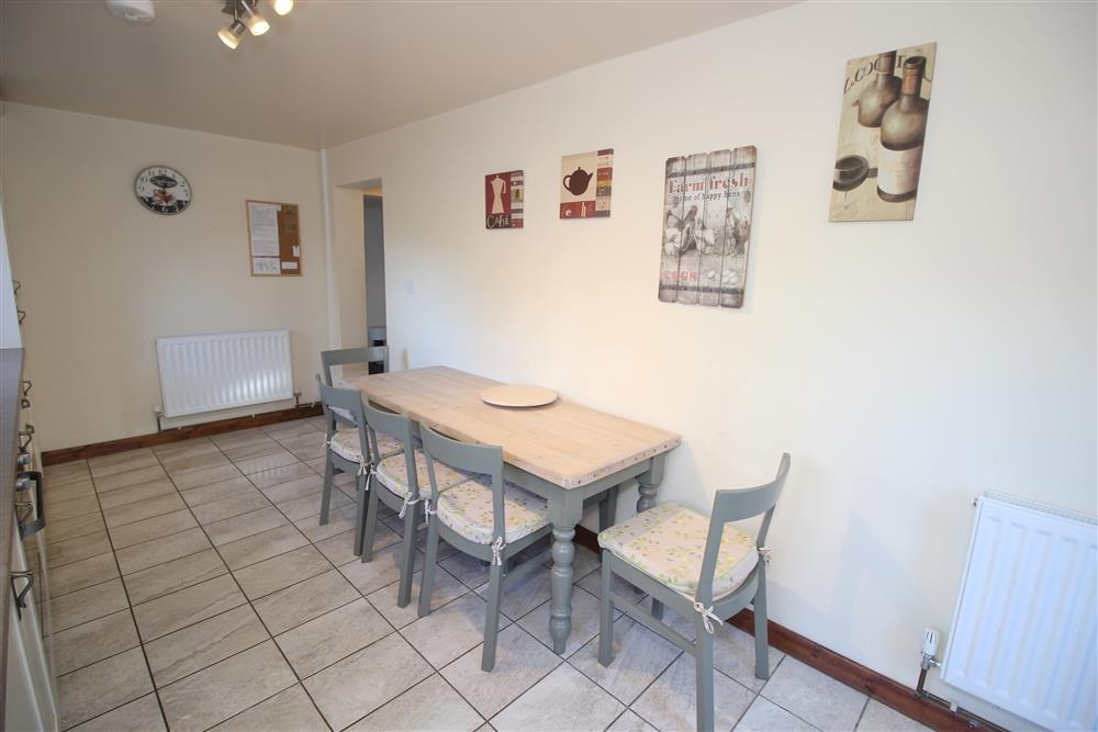 There are 5 chairs and one long bench for the dining table in the Kitchen