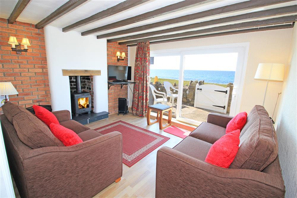 Lounge area with log burner, patio doors and views out to sea