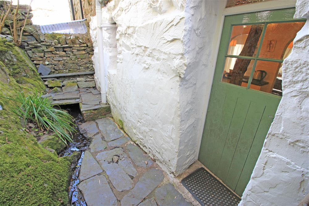 Back door from the kitchen to the small slate path to the rocky steps up to the back garden.