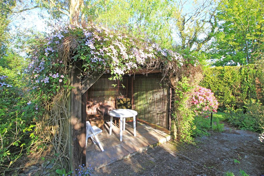 The hideaway in the garden with table and chairs