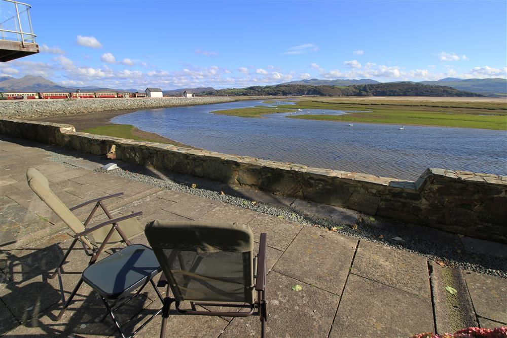 Shared patio area with views of the estuary. On the left handside of this photo you can see the Steam Trains red railway carrages.