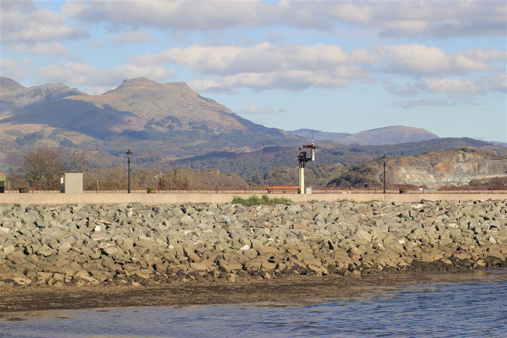 Close up photo of the 'Cob', the railway line which the Steam Trains use and Snowdonia mountins in the distance