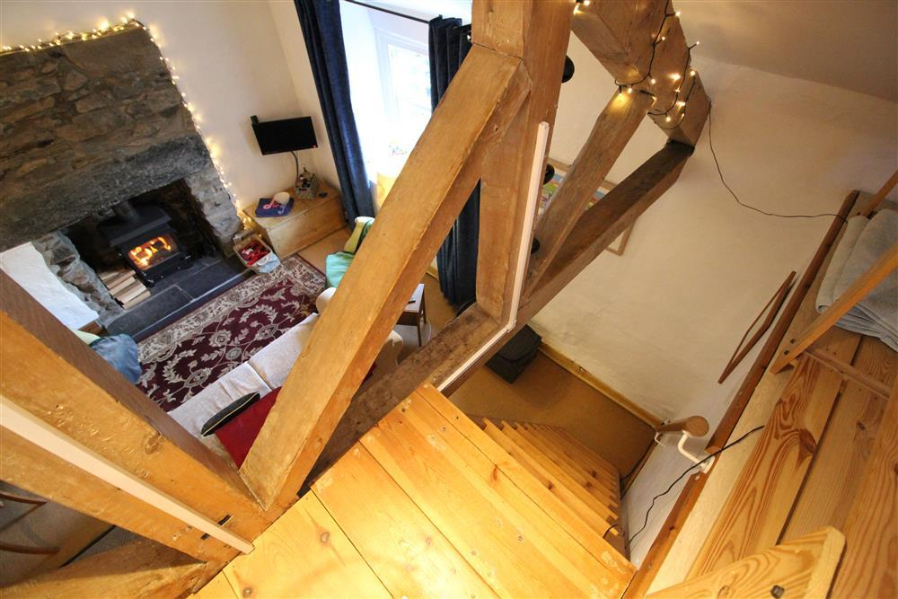 Photo from above the stairs to crog loft (Bedroom 3) looking down to the Living Room. Open stairs which are slightly narrower and steeper than usual and open roof trusses to lounge space. Not suitable for young children or the infirm.