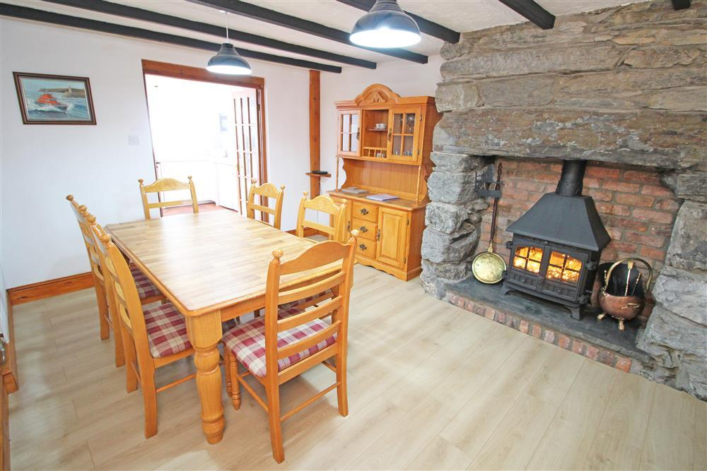 Photo of the Dining Area with table with seating for 6 with a decorative wood burner with flicker effect lights. The doorway in this photo is for the Kitchen (Ground Floor)