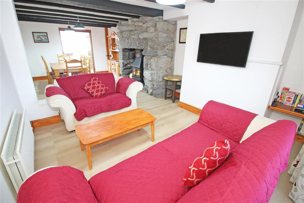 Photo of the Lounge Area with 2 cream comfy sofas, decorative wood burner with flicker effect lights,  flat screen smart tv and a table with seating for 6. (Ground Floor)