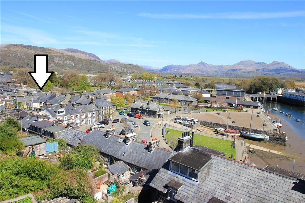 Photo looking across the harbour town of Porthmadog towards the Snowdonia mountains. The arrow shows where Siop Da Da is in the town.