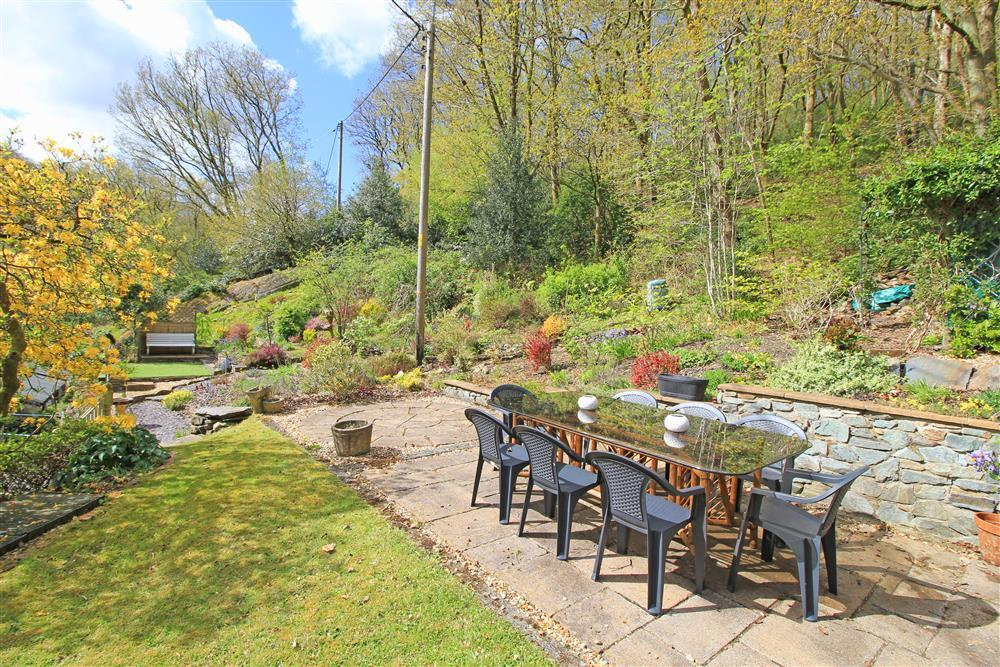 Big back garden with dining area, sitting area and bench. This amazing garden has access to the wild woodland above.