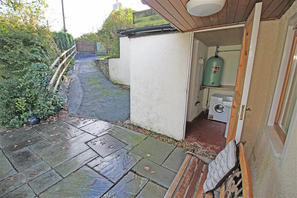Outbuilding with washing machine and the path that leads up to the car park area.