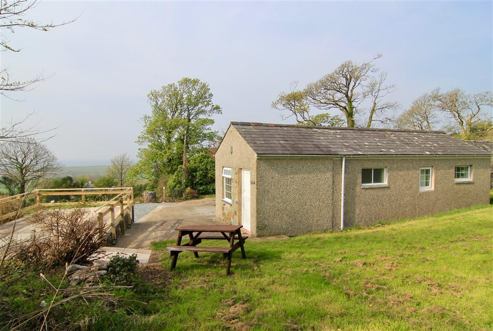 Side view of Min y Mor cottage, picnic table and the private patio area to the left in the photo.