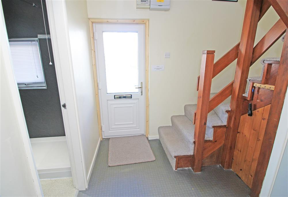 Photo of the front door with the 'u' shaped staircase to the right. The doorway to the left hand side of the front door is to the Shower Room.