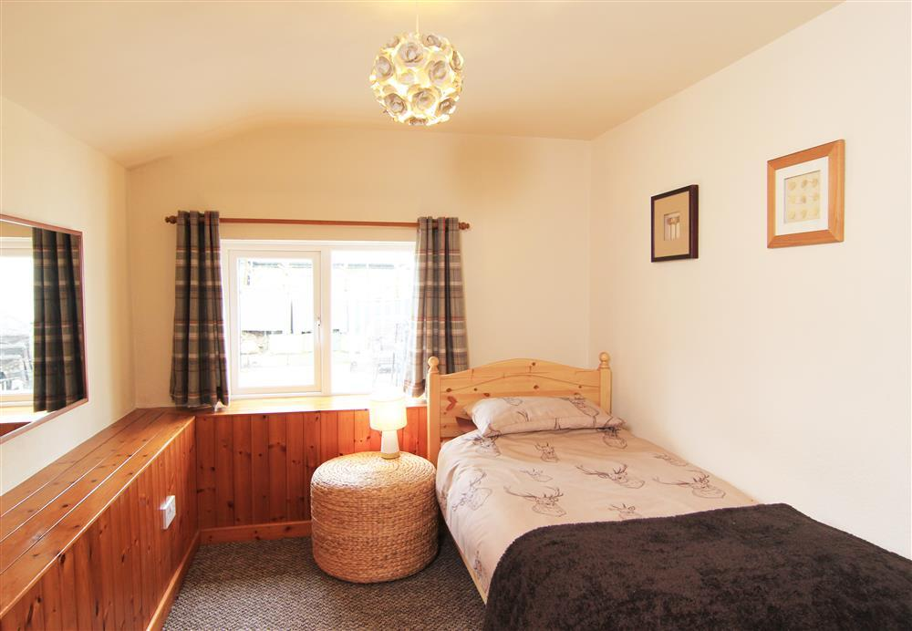 Single bedroom with views of the garden and patio area.