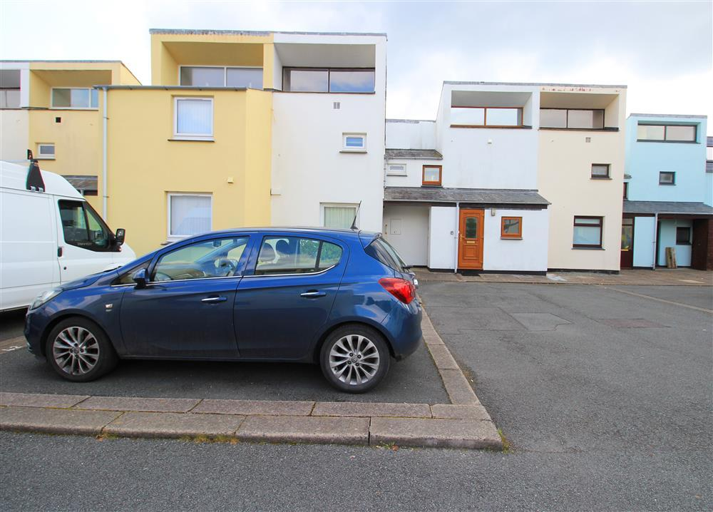 The blue car is in the car park space and the light brown front door is for the apartment.
