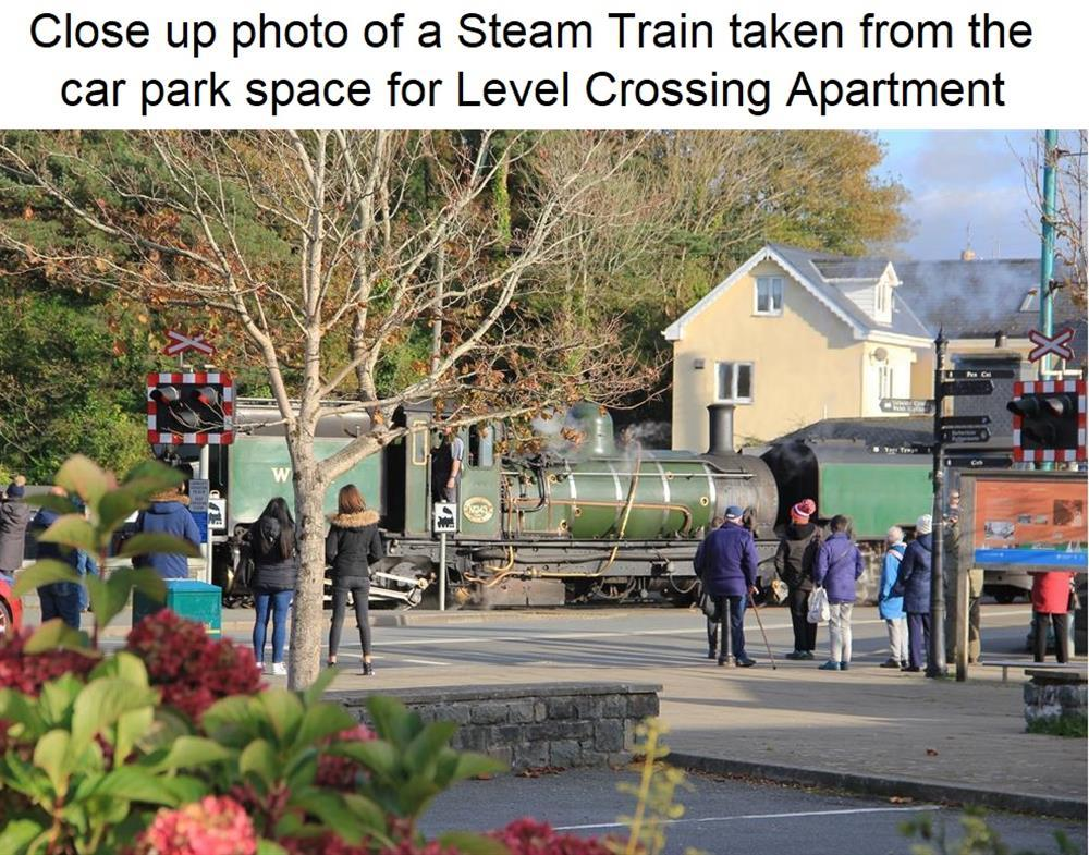 This close up photo was taken from the Car Park Space for Level Crossing apartment of Welsh Highland Steam Train crossing the road in Porthmadog.