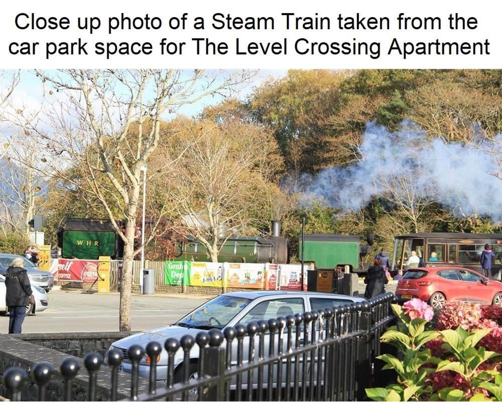 Photo taken from the Car Park Space for Level Crossing apartment of Welsh Highland Steam Train crossing the road