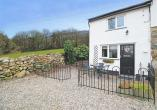 Front of Dowlais Cottage with a gate to the enclosed front garden with outside table & chairs. You park your car on the gravel infront of the cottage