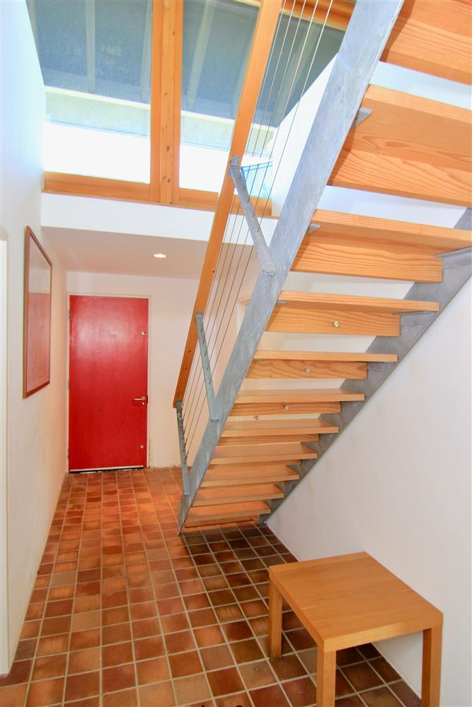 This photo is showing the entance hall on the ground floor. The red door is the front door and the staircase takes you up to the Living room.