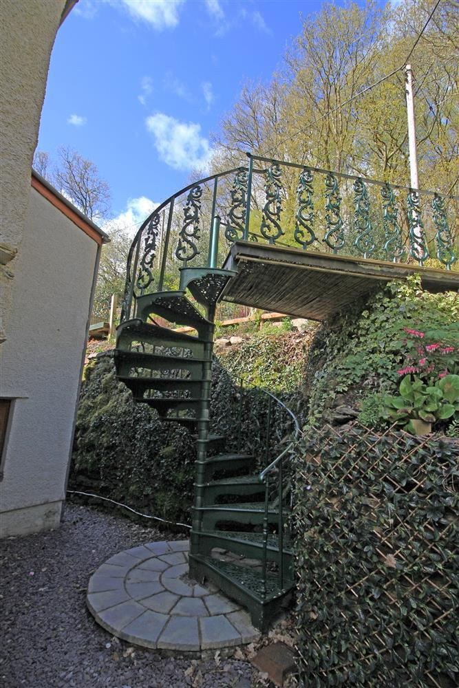 There are two staircases to get to the garden and woodland. A green spiral staircase close to the back door and steps next to that car park area.