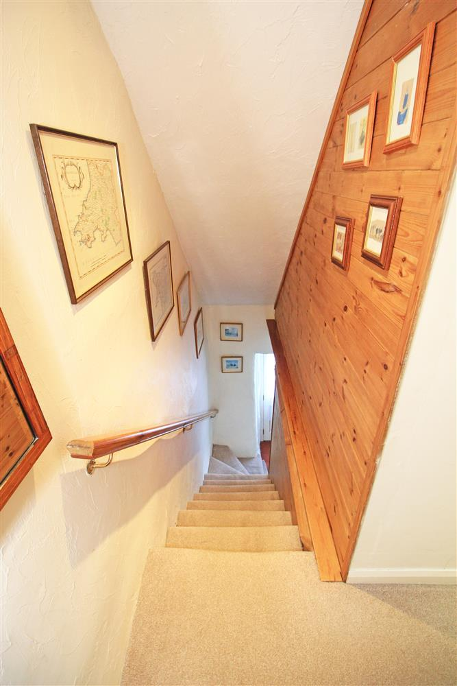 Photo from the top of the starcase looking down the stairs and the front door.