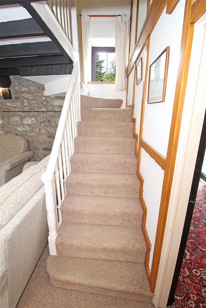 The bottom of the staircase in the Farmhouse on the ground floor in the lounge. This staircase takes you up bathroom 1 and bedrooms 1, 2 & 3.