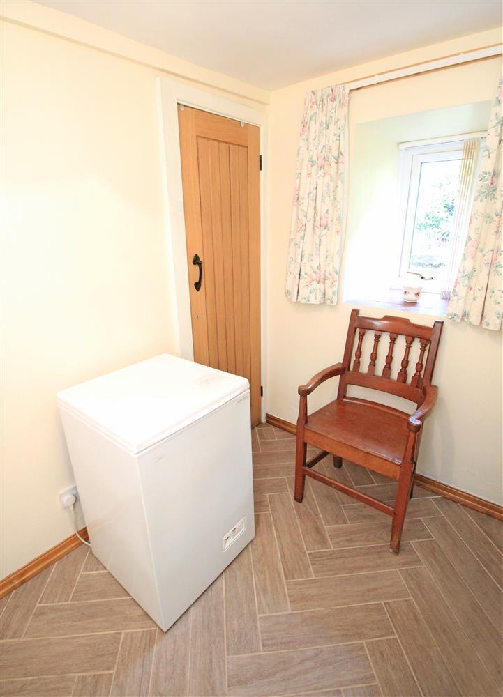 Small room on the ground floor where the chest freezer and cleaning equipment are kept.