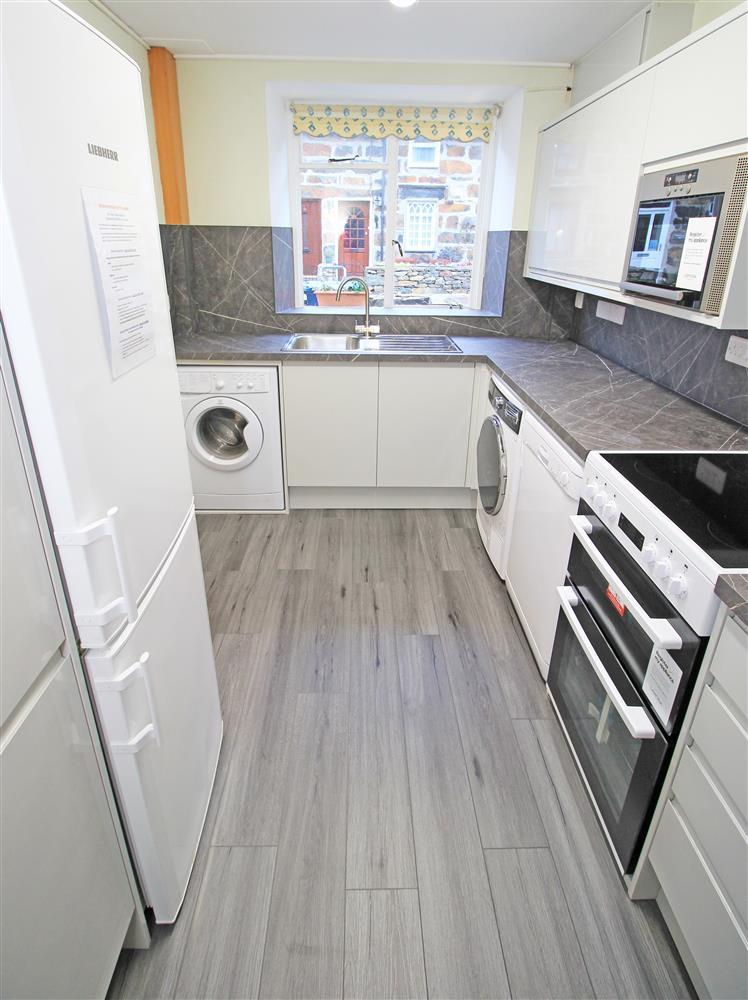 Kitchen is a galley style with fitted units, electric cooker, fridge, freezer, microwave, dishwasher, washing machine and tumble dryer.