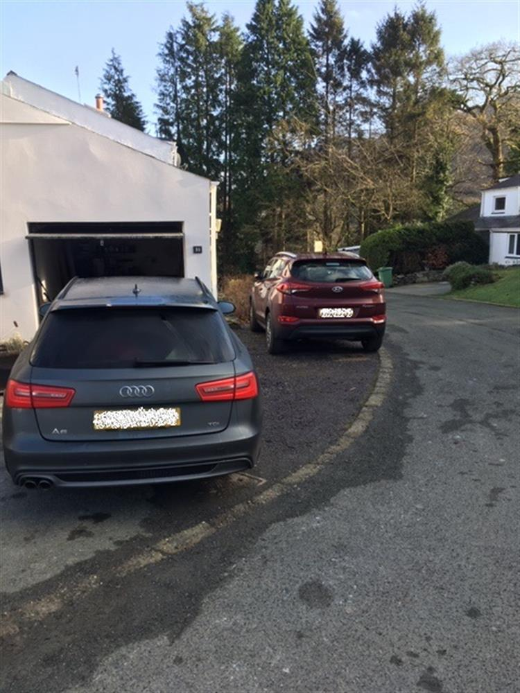 Parking to the left of the property for 2 cars. Space in front of the garage and on the slate to the side.